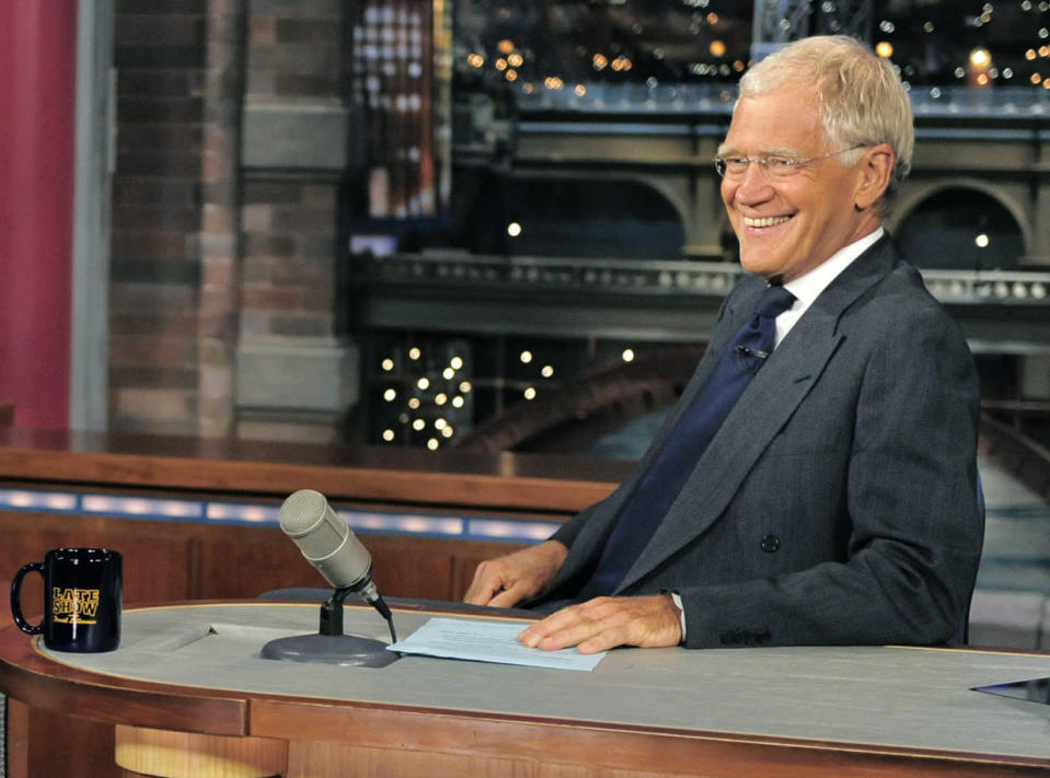 """FILE - In this July 16, 2013 file photo, host David Letterman smiles on the set of the """"Late Show with David Letterman."""" A study released Monday of gags made by late-night comics found that Obama and Democrats provided the lion's share of punchlines during the first six months of the year. That's an abrupt change from 2012, when Mitt Romney proved a gift to the comic gods. (AP Photo/CBS, John Paul Filo) MANDATORY CREDIT; NO ARVHIVE; NO SALES; FOR NORTH AMERICAN USE ONLY"""