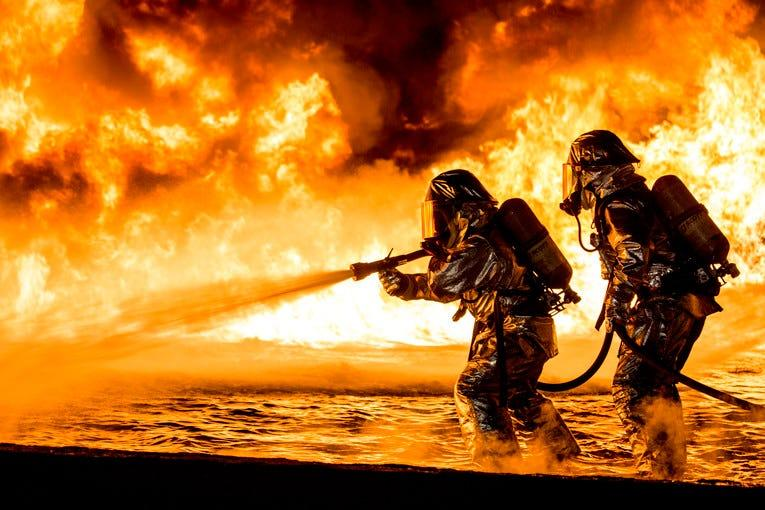 Marines use a fire hose to extinguish a fuel fire during live-burn training at Marine Corps Air Station Futenma in Okinawa, Japan, Jan. 25, 2019.