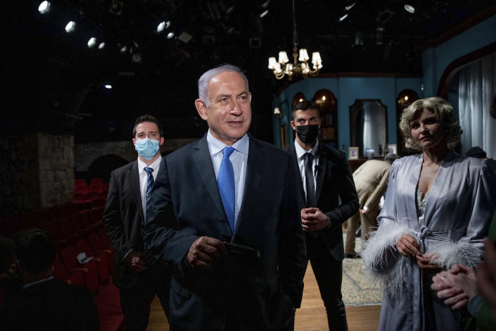 Israeli Prime Minister Benjamin Netanyahu meets Israeli actress Carmit Mesilati Kaplan, right, during a visit to the Khan theater ahead of the re-opening of the culture sector, in Jerusalem on Tuesday, Feb. 23, 2021. (Ohad Zwigenberg/Pool Photo via AP)