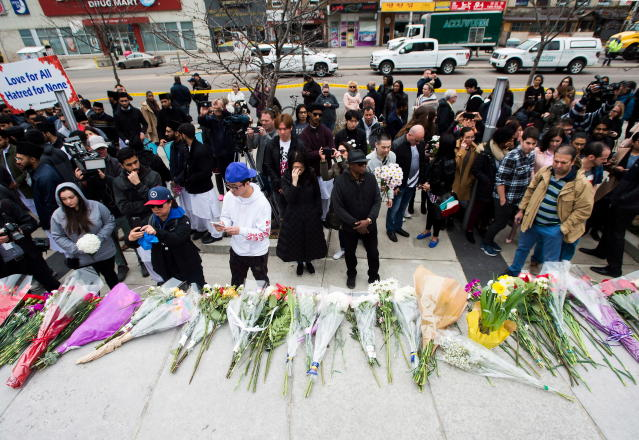 <p>People pay tribute at a memorial along Yonge Street, Tuesday, April 24, 2018, in Toronto, the day after a driver drove a van down sidewalks, striking and killing numerous pedestrians in his path. (Photo: Nathan Denette/The Canadian Press via AP) </p>