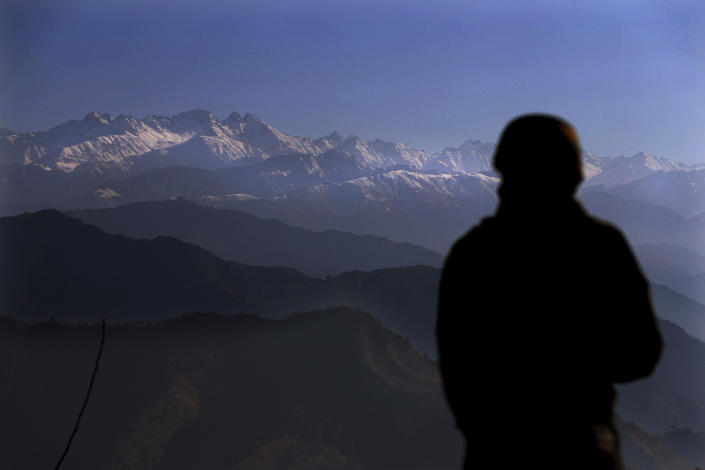 An Indian army soldier looks towards the snow-covered Pir Panjal range of mountains from one of their forward post at the Line of Control (LOC) between India and Pakistan border, in Poonch, about 248 kilometers (155 miles) from Jammu, India, Wednesday, Dec. 16, 2020. From sandbagged Indian army bunkers dug deep into the Pir Panjal mountains in the Himalayas, villages on the Pakistan-controlled side of Kashmir appear precariously close, on the other side of the Line of Control that for the past 73 years has divided the region between the two nuclear-armed rivals. Tens of thousands of soldiers from India and Pakistan are positioned along the two sides. The apparent calm is often broken by the boom of blazing guns, with each side accusing the other of initiating the firing. (AP Photo/Channi Anand)