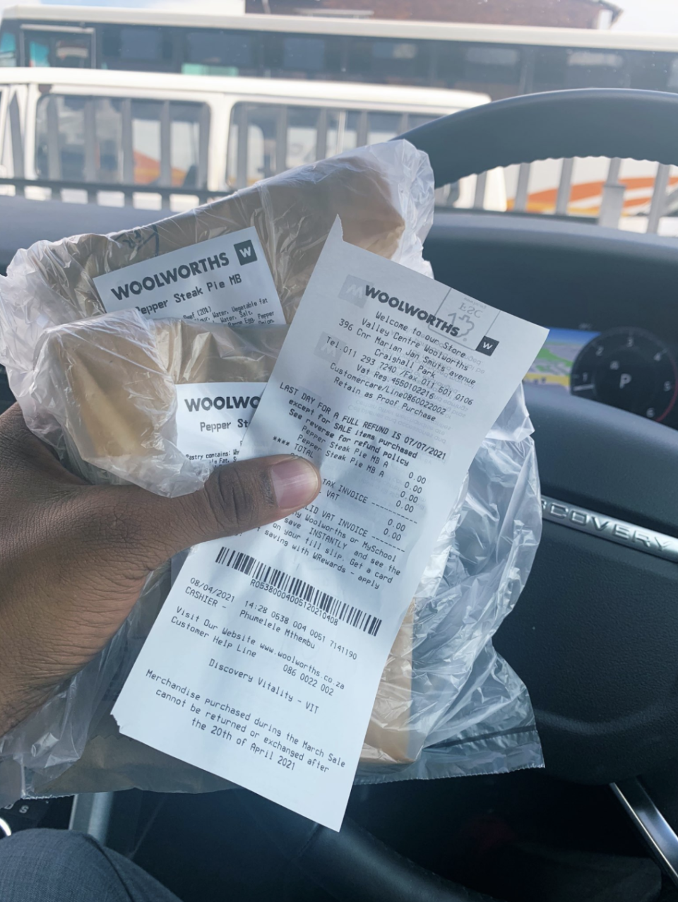 Photo of a hand holding two pies and a Woolworths SA receipt.