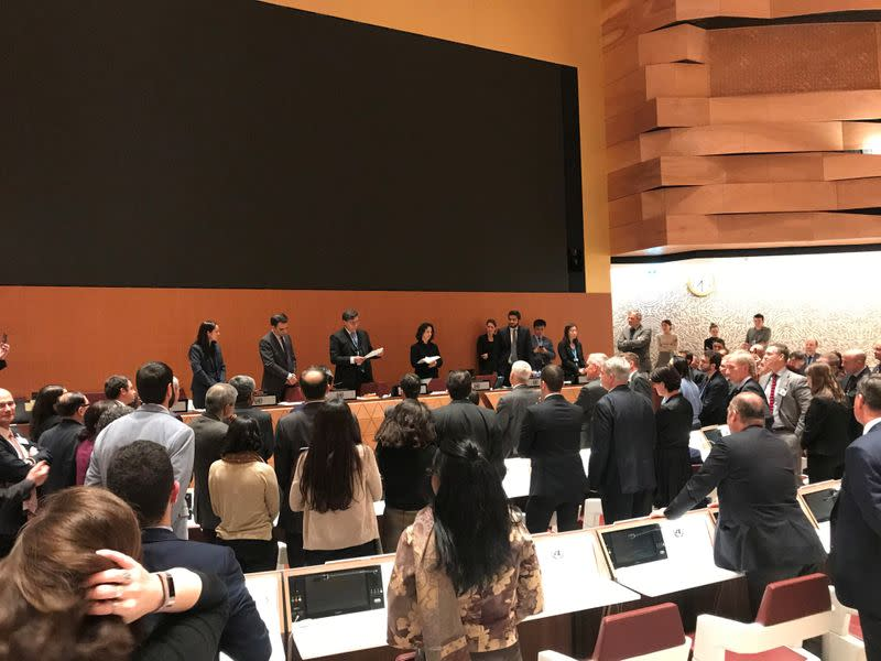 Delegates gather around an empty screen at a meeting on lethal autonomous weapons in the United Nations in Geneva