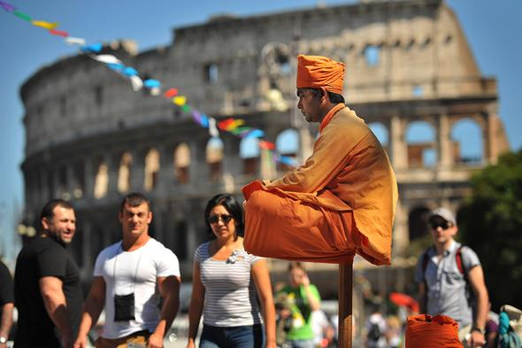 ROME, ITALY - MAY 14:  A street performer gets second glances as he appears to sit solely on a pole near the Colosseum on Tuesday May 14, 2013 in Rome, Italy.  (Photo by Matt McClain/ The Washington Post)