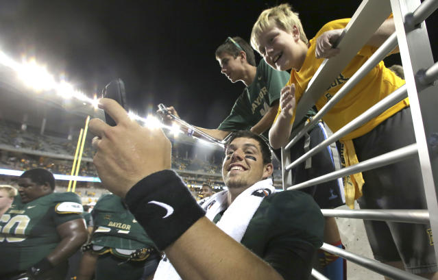 Baylor quarterback Bryce Petty takes a self photo with a fan after an NCAA college football game against SMU Sunday, Aug. 31, 2014, in Waco, Texas. Despite only playing two quarters, Petty threw for two touchdowns and ran for another score, helping No. 10 Baylor open its riverfront campus stadium with a 45-0 victory over former Southwest Conference rival SMU. (AP Photo/LM Otero)