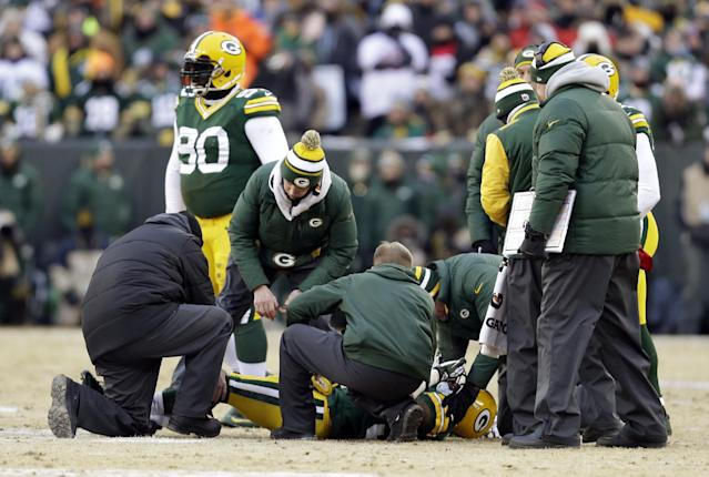 Trainers check on Green Bay Packers cornerback Sam Shields (37) during the first half of an NFL wild-card playoff football game against the San Francisco 49ers, Sunday, Jan. 5, 2014, in Green Bay, Wis. (AP Photo/Mike Roemer)