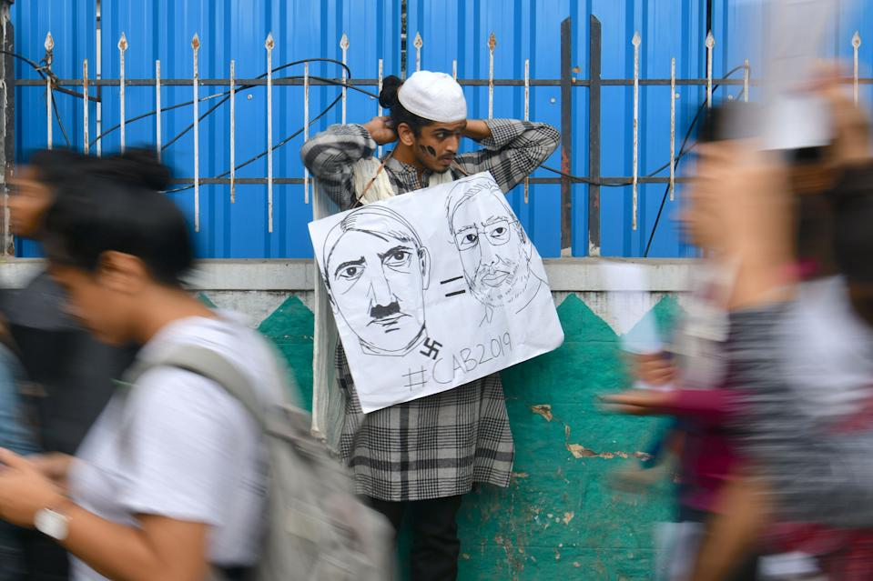 A man holds a placard comparing Indian Prime Minister Narendra Modi to German chancellor and Nazi Party leader Adolf Hitler at a protest against India's new citizenship law in Bangalore on December 17, 2019. - Fresh protests against India's new citizenship law erupted December 17 as alleged police brutality fuelled fury against the legislation which critics say is anti-Muslim. (Photo by Manjunath Kiran / AFP) (Photo by MANJUNATH KIRAN/AFP via Getty Images)