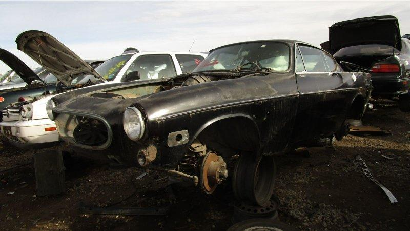 """<p>The <a href=""""https://www.autoblog.com/2013/09/18/irv-gordons-volvo-p1800-has-hit-3-million-miles/"""" data-ylk=""""slk:highest-mileage one-owner car in the world"""" class=""""link rapid-noclick-resp"""">highest-mileage one-owner car in the world</a> happens to be a <a href=""""https://en.wikipedia.org/wiki/Volvo_P1800"""" rel=""""nofollow noopener"""" target=""""_blank"""" data-ylk=""""slk:Volvo P1800"""" class=""""link rapid-noclick-resp"""">Volvo P1800</a>, which makes sense when you take a look at the agricultural-equipment-simple hardware under the sinuous sheet-metal of one of these cars. You'd think that P1800s wouldn't show up in cheap self-service wrecking yards, but you'd be wrong— here's a battered but fairly intact '71 in<a href=""""https://upullandpay.com/denver/home/"""" rel=""""nofollow noopener"""" target=""""_blank"""" data-ylk=""""slk:a Denver yard"""" class=""""link rapid-noclick-resp""""> a Denver yard</a>. <a href=""""https://www.autoblog.com/2017/12/01/junkyard-gem-1971-volvo-p1800/"""" data-ylk=""""slk:Read more"""" class=""""link rapid-noclick-resp""""><em>Read more</em></a>.</p>"""