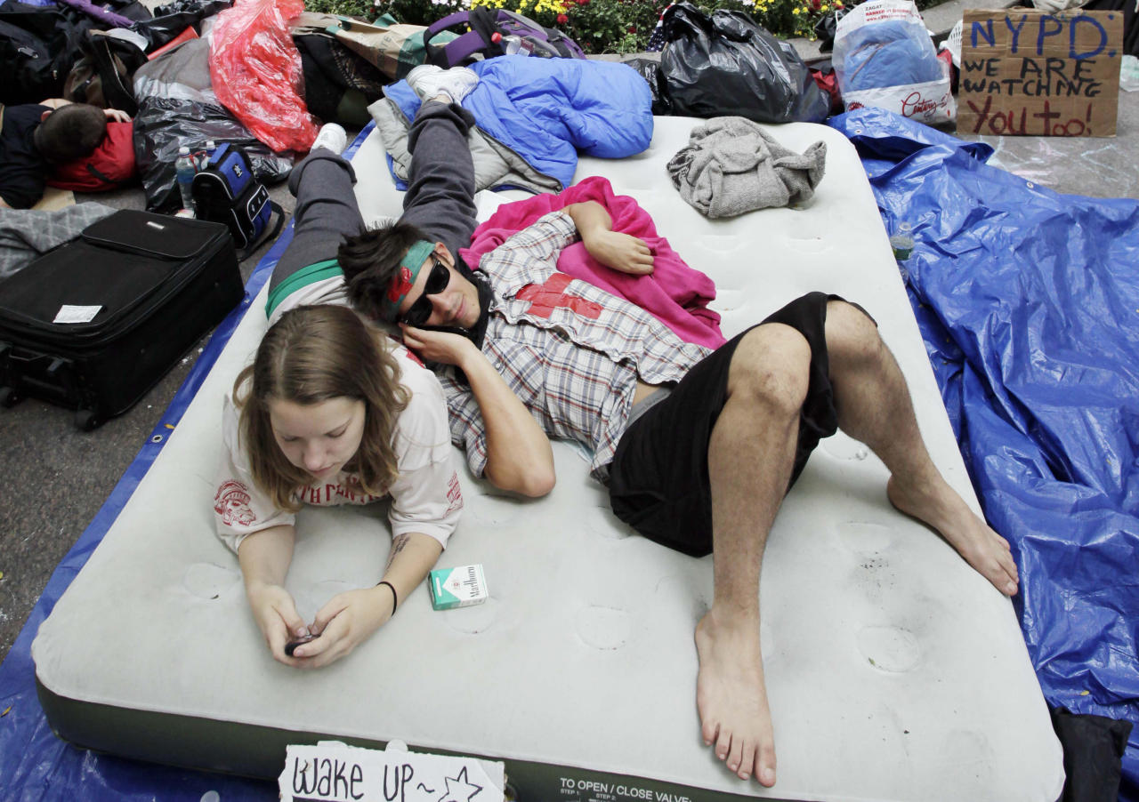 FILE - In this Sept. 26, 2011, file photo, Amber Oestreich, left, and Robert Grodt, who are part of the protest movement Occupy Wall Street, rest on a mattress in New York's Zuccotti Park. People's Protection Units, also known by their Kurdish initials as the YPG, a U.S.-backed Syrian Kurdish militia, said Tuesday, July 11, 2017, that two American volunteers were killed fighting the Islamic State group in northern Syria last week. (AP Photo/Mark Lennihan, File)