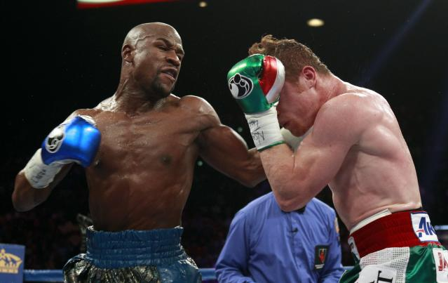 Floyd Mayweather Jr. of the U.S. punches at WBC/WBA 154-pound champion Canelo Alvarez during their title fight in Las Vegas