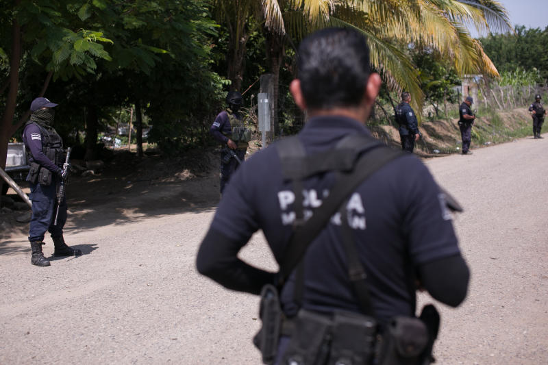 Mexican police man at a check point after a clash between armed groups in Tepalcatepec, Michoacan state, Mexico, Saturday, Aug. 31, 2019. Heavily armed bands clashed Friday in Tepalcatepec, leaving at least 9 dead, according to authorities. (AP Photo/Armando Solis)