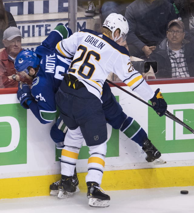 Buffalo Sabres defenseman Rasmus Dahlin (26) puts Vancouver Canucks center Tyler Motte (64) into the boards during the second period of an NHL hockey game Friday, Jan. 18, 2019, in Vancouver, British Columbia. (Jonathan Hayward /The Canadian Press via AP)