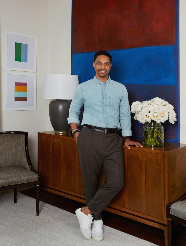 Risdon poses in his living room next to a console table he purchased at Kamelot Auctions in Philadelphia. The large canvas work beside him is by Jaime Karf; the smaller framed acrylics behind him are by William Radawec. Fox Mill Lighting & Supply Co. produced the table lamp.