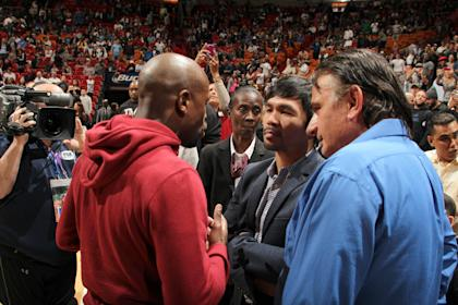 Floyd Mayweather (L), Manny Pacquiao (M) and Michael Koncz (R) speak at an NBA game in Miami, Fla., on Jan. 27.