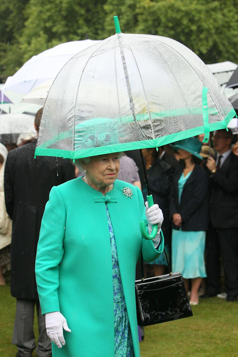 Britain's Queen Elizabeth II shelters from the rain under an umbrella as she hosts a garden party at Buckingham Palace, in central London. (Photo by Dominic Lipinski/PA Images via Getty Images)