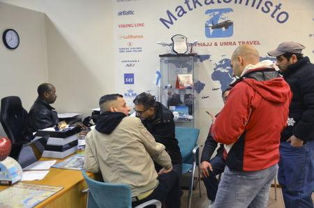 Travel agent Muhiadin Hassan (L) helps a group of migrants to arrange for flights to Baghdad at his office in Helsinki, Finland, February 10, 2016. REUTERS/Tuomas Forsell