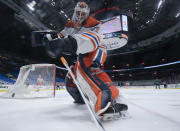 Edmonton Oilers goaltender Mike Smith plays the puck during the first period of an NHL hockey game against the Vancouver Canucks on Thursday, Feb. 25, 2021, in Vancouver, British Columbia. (Jonathan Hayward/The Canadian Press via AP)