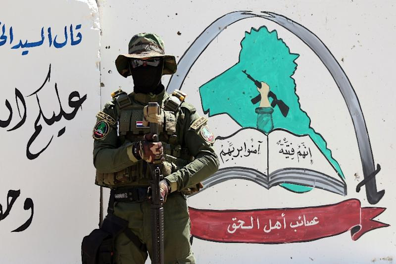 An Iraqi fighter of the Shiite militia Asaib Ahl al-Haq (The League of the Righteous) stands guard outside the militia's headquarters in Basra, on May 18, 2015 (AFP Photo/Haidar Mohammed Ali)