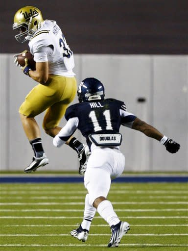 UCLA running back Steven Manfro (33) completes a pass against Rice safety Malcolm Hill (11) during the second half of an NCAA college football game, Thursday, Aug. 30, 2012, in Houston. UCLA won 49-24. (AP Photo/Eric Kayne)