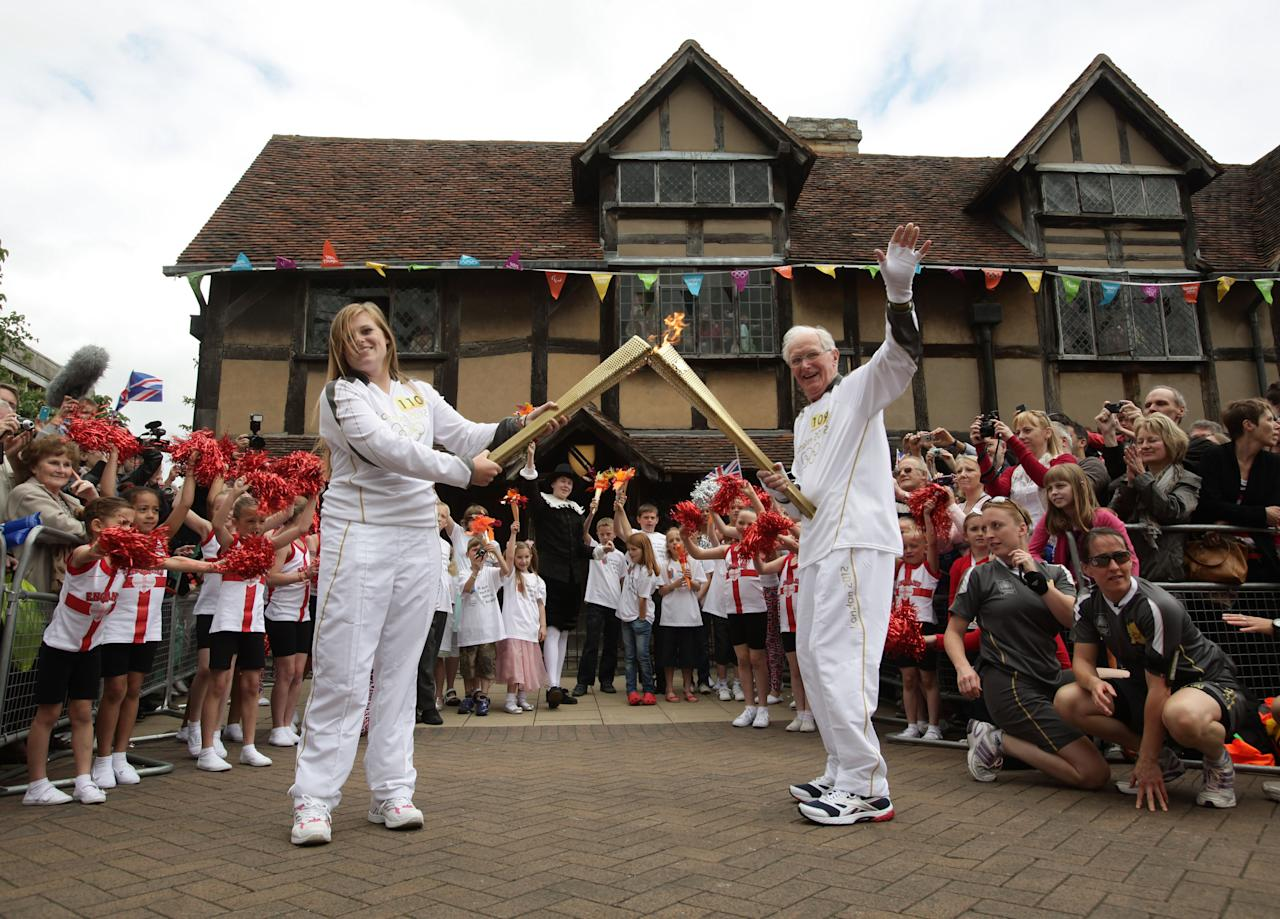 STRATFORD-UPON-AVON, UNITED KINGDOM - JULY 1:  In this handout image provided by LOCOG, Torchbearer 109 Peter Wyatt passes the Olympic Flame to Torchbearer 110 Camilla Hadland outside Shakespeare's Birthplace in Stratford-Upon-Avon during day 44 of the Olympic Flame Torch Relay on July 1, 2012 in Stratford-upon-Avon, England. The Olympic Flame is now on day 44 of a 70-day relay involving 8,000 torchbearers covering 8,000 miles.  (Photo by LOCOG via Getty Images)