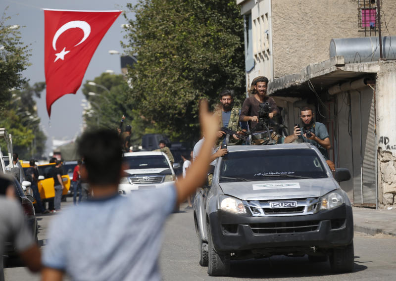 Local residents cheer as Turkish-backed Syrian opposition fighters drive around the border town of Akcakale, Sanliurfa province, southeastern Turkey, on their way to Tal Abyad, Syria, Monday, Oct. 14, 2019. Syrian troops entered Monday several northern towns and villages getting close to the Turkish border as Turkey's army and opposition forces backed by Ankara marched south in the same direction raising concerns of a clash between the two sides as Turkey's invasion of northern Syria entered its sixth day. (AP Photo/Lefteris Pitarakis)