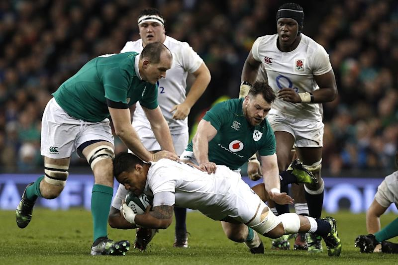 England's Nathan Hughes is tackled by Ireland's Cian Healy (C) and Devin Toner (L) during the Six Nations international rugby union match March 18, 2017