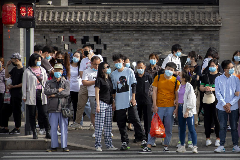 People wearing face masks to protect against the spread of the new coronavirus wait to cross an intersection in Beijing, Saturday, May 16, 2020. According to official data released on Saturday India's confirmed coronavirus cases have surpassed China's. (AP Photo/Mark Schiefelbein)