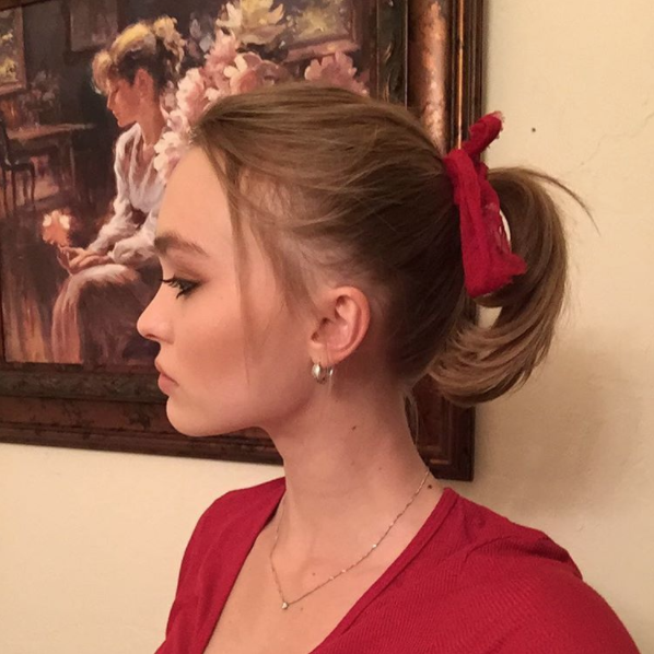 "This curled-under pony is adorable, but <a href=""https://www.glamour.com/gallery/hair-ribbon-bow-ideas?mbid=synd_yahoo_rss"" rel=""nofollow noopener"" target=""_blank"" data-ylk=""slk:the red ribbon"" class=""link rapid-noclick-resp"">the red ribbon</a> is what brings Lily-Rose Depp's entire ensemble to life."