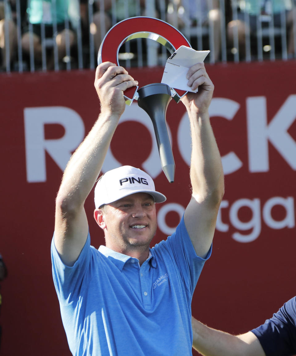Nate Lashley raises the winner's trophy after the final round of the Rocket Mortgage Classic golf tournament, Sunday, June 30, 2019, in Detroit. (AP Photo/Carlos Osorio)