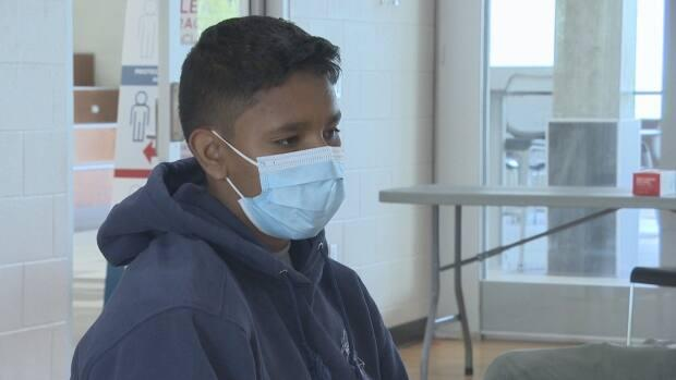 Rashawn Taniskishayinew, 14, is the first in his family to get a COVID-19 vaccine.