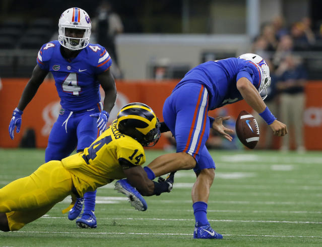 Michigan safety Josh Metellus (14) strips the ball from Florida quarterback Feleipe Franks (13) after a short run by Franks as wide receiver Brandon Powell (4) watches in the second half of an NCAA college football game, Saturday, Sept. 2, 2017, in Arlington, Texas. (AP Photo/Tony Gutierrez)