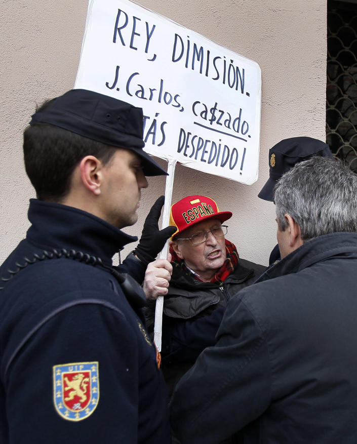 """Police men talk to a protestor, centre, who shows a banner reading """"King, resign! Juan Carlos, hunted, you are fired"""" as Spain's King Juan Carlos leaves from San Jose hospital where he received medical treatment in Madrid, Spain, Wednesday, April 18, 2012. Spain's King Juan Carlos says he is sorry for having gone on African elephant-hunting trip. In an unprecedented gesture, the 74-year-old monarch said he was """"very sorry. I made a mistake. It won't happen again."""" The king came under scathing criticism this week after he went on a safari trip to Botswana as Spain writhes in its one of its worst ever economic crises. The trip came to light when the king ended up having to be taken to hospital for hip treatment after having fallen. (AP Photo/Andres Kudacki)"""