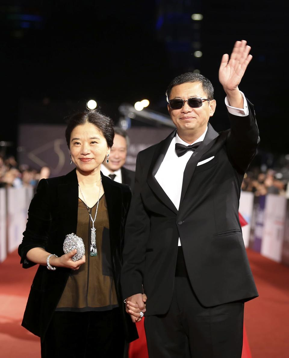 Hong Kong director Wong Kar-wai (R) and his wife pose for photographers on the red carpet at the 50th Golden Horse Film Awards in Taipei November 23, 2013. REUTERS/Patrick Lin (TAIWAN - Tags: ENTERTAINMENT)