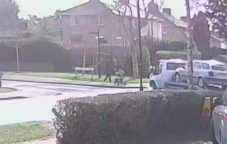 A van transporting a car on a trailer turns in front of the mother and her baby. (SWNS)