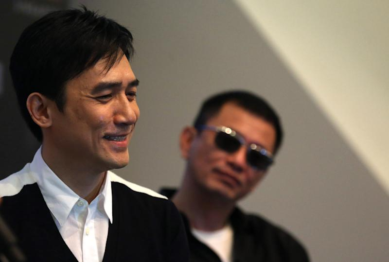 "Movie director Wong Kar-wai, right, watches from the background as Tony Leung, left, speaks during a press conference on Wednesday, Jan. 23, 2013 in Singapore. For a director and actor who have worked together for about two decades, there did not seem to be much chemistry between Wong and Leung at the news conference promoting their new movie ""The Grandmaster."" (AP Photo/Wong Maye-E)"