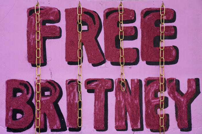 """A """"Free Britney"""" sign is decorated with chains outside a court hearing concerning pop singer Britney Spears' conservatorship at the Stanley Mosk Courhouse, Thursday, Feb. 11, 2021, in Los Angeles. (AP Photo/Chris Pizzello)"""