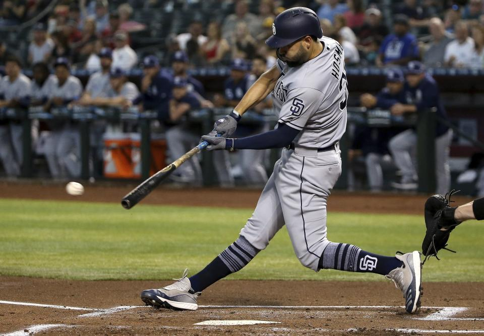 San Diego Padres' Eric Hosmer connects for a two-run single against the Arizona Diamondbacks during the first inning of a baseball game Saturday, April 13, 2019, in Phoenix. (AP Photo/Ross D. Franklin)