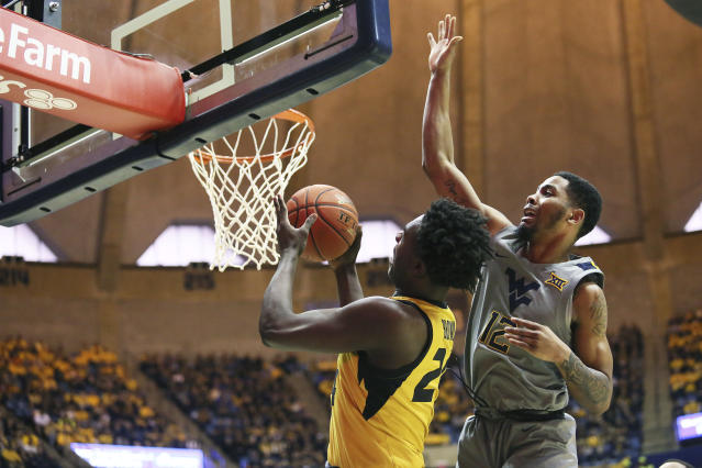 Missouri forward Kobe Brown (24) goes to make a shot as he is defended by West Virginia guard Taz Sherman (12) during the first half of an NCAA college basketball game Saturday, Jan. 25, 2020, in Morgantown, W.Va. (AP Photo/Kathleen Batten)