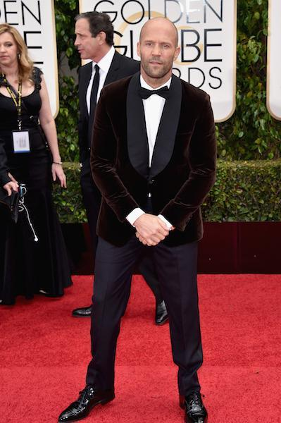 Jason Statham wearing a chocolate-colored velvet jacket at the 73rd Golden Globe Awards.