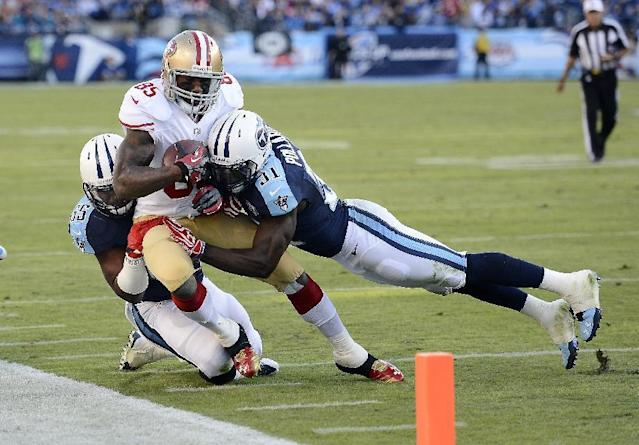 San Francisco 49ers tight end Vernon Davis (85) is knocked out of bounds by Tennessee Titans defenders Bernard Pollard (31) and Zach Brown, left, in the second half an NFL football game on Sunday, Oct. 20, 2013, in Nashville, Tenn. (AP Photo/Mark Zaleski)