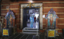 An employee sanitises a Hindu temple in Mumbai, India, Sunday, Nov. 15, 2020. India is second in the world in total reported coronavirus cases behind the U.S., but daily infections have been on the decline since the middle of September. (AP Photo/Rafiq Maqbool)