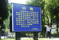 A resident passes by a display warning residents about the dangers of a suspected runaway leopard in the area in Hangzhou in eastern China's Zhejiang province Sunday, May 9, 2021. A search for the last of three leopards that escaped from a safari park in eastern China was ongoing, authorities said Monday, May 10, 2021 as the park came under fire for concealing the breakout for nearly a week. (Chinatopix via AP)