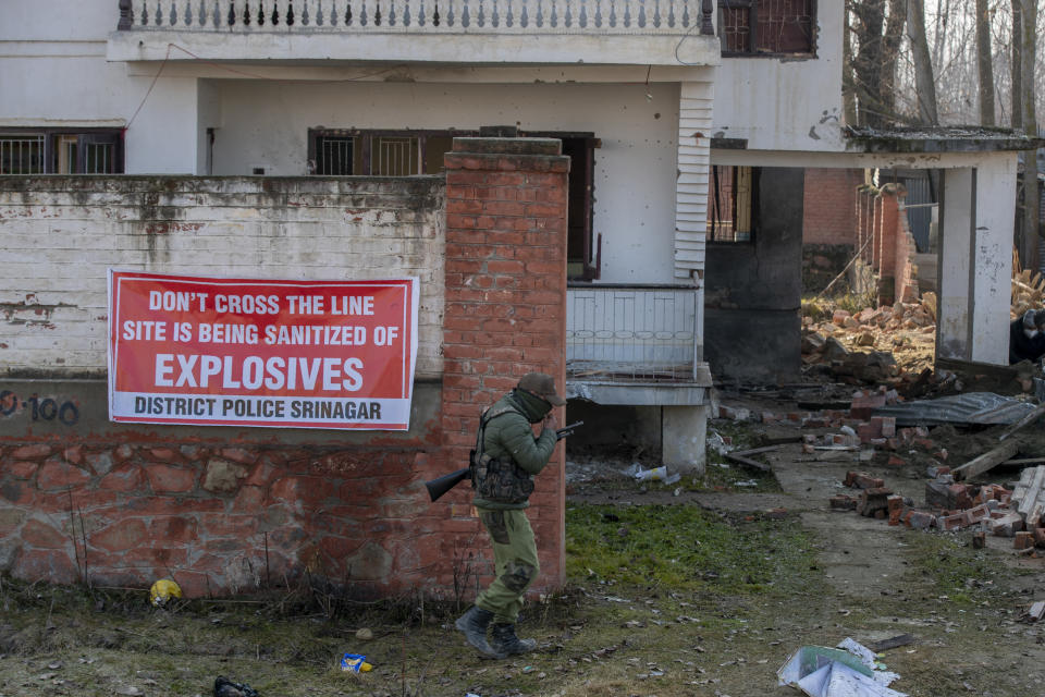 Indian policeman walk back after hanging a banner on the wall of a house damaged in a gun battle on the outskirts of Srinagar, Indian controlled Kashmir, Wednesday, Dec. 30, 2020. A gun battle between rebels and government forces overnight killed three rebels on the outskirts of Srinagar on Wednesday, officials said. (AP Photo/ Dar Yasin)