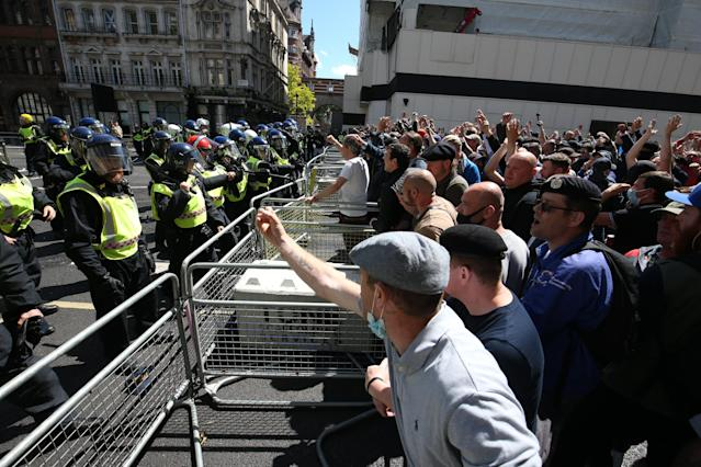 Police are confronted by protesters claiming to defend statues in central London on Saturday. (PA)