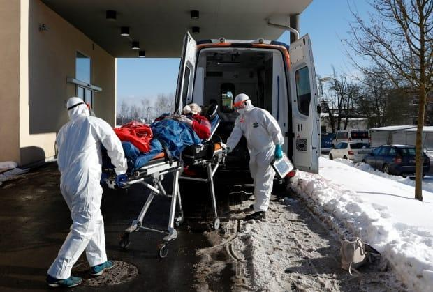 Medical workers move a COVID-19 patient into an ambulance at a hospital overrun by the disease in Cheb, Czech Republic, on Feb. 12. The small city near the German border has a death rate six times the national average.