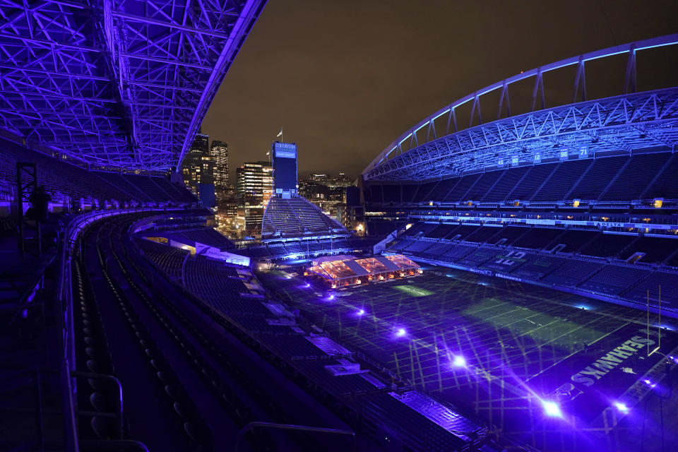 """Colored lights glow as night falls while people eat dinner in an outdoor dining tent set up at Lumen Field, the home of the Seattle Seahawks NFL football team, Thursday, Feb. 18, 2021, in Seattle. The """"Field To Table"""" event was the first night of several weeks of dates that offer four-course meals cooked by local chefs and served on the field at tables socially distanced as a precaution against the COVID-19 pandemic, which has severely limited options for dining out at restaurants in the area. (AP Photo/Ted S. Warren)"""