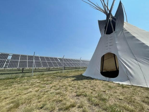 New solar panels stand in front of the education center at Cowessess First Nation in Saskatchewan. Energy from these and other panels will offset the consumption of five buildings in the community.  (Mickey Djuric/CBC - image credit)