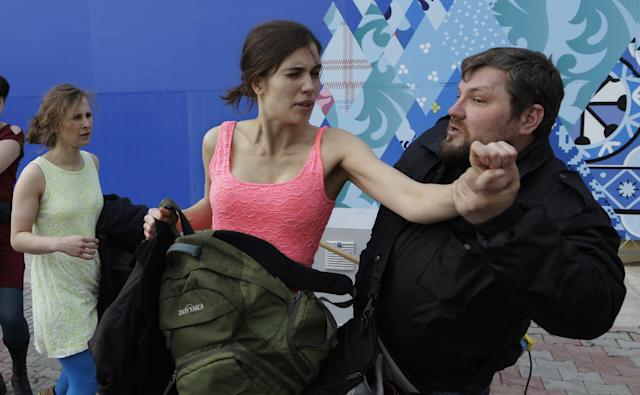 A russian security officer attacks Nadezhda Tolokonnikova and a photographer as she and fellow members of the punk group Pussy Riot, including Maria Alekhina, left, stage a protest performance in Sochi, Russia, on Wednesday, Feb. 19, 2014. The group had gathered in a downtown Sochi restaurant, about 30km (21miles) from where the Winter Olympics are being held. They ran out of the restaurant wearing brightly colored clothes and ski masks and were set upon by about a dozen Cossacks, who are used by police authorities in Russia to patrol the streets