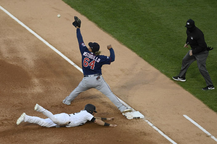 Minnesota Twins first baseman Willians Astudillo (64) catches the throw to double off Chicago White Sox's Adam Eaton (12) at first base during the first inning of a baseball game Tuesday, May 11, 2021, in Chicago. (AP Photo/Paul Beaty)