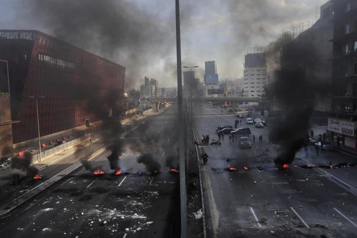 Black smoke rise from burned tires set by protesters to block a main highway, during a protest in the town of Jal el-Dib, north of Beirut, Lebanon, Monday, March 8, 2021. The dayslong protests intensified Monday amid a crash in the local currency, increase of consumer goods prices and political bickering between rival groups that has delayed the formation of a new government. (AP Photo/Hussein Malla)